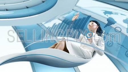 Future lifestyle. Sexy brunette sits in the futurisctic armchair. Working with transparent touch screen interface. Concept of computer operator workplace in the future / space ship or another planet.