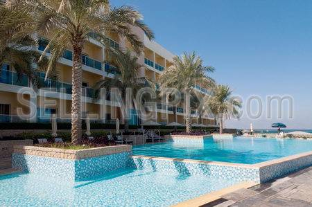 Stylish outdoor pool in luxury hotel. Palms, beach chairs and sun umbrellas. Hotel building and ocean shore.