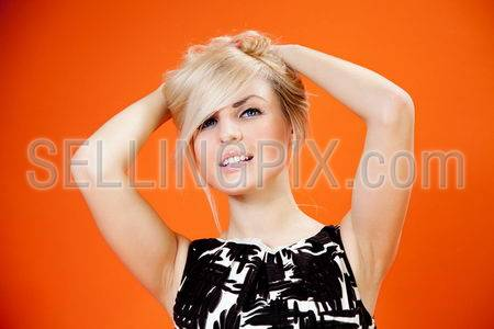 Charming blonde is looking at you! Lady against orange background wearing fashionable b/w dress studio shot.