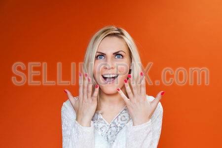Amazing sexy blonde! Lady against orange background wearing fashionable  dress studio shot.