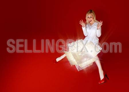 Present for a charming blonde! Sense of holiday. Gift box in center. Light beams and stars coming from the box. Red background. Amazing face expression.