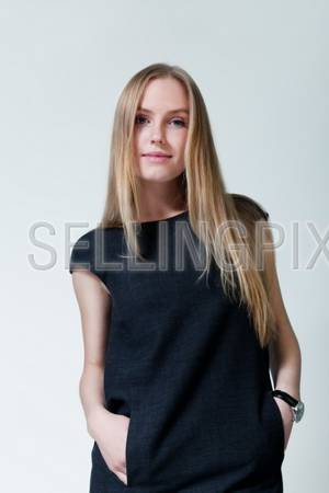 Pretty lady wearing fashionable dress. Fresh new young face. Studio shot, uniform background.