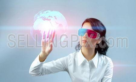 Fascinating brunette wearing 3d anaglyph stereo glasses. Operating futuristic 3d interface. Touching three-dimensional globe. One of a series.
