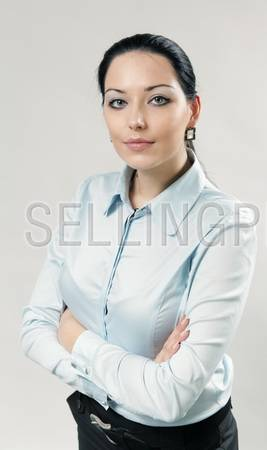 Sexy brunette businesswoman / assistant / secretary portrait. Girl folded her arms. Wearing white shirt and black skirt. One of a series.