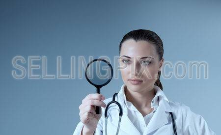 Young female doctor holding magnifying glass in right hand. Empty space to place your logo / text / product. Medical / pharmaceutical research concept. Healthcare collection.